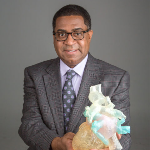 Dr Laws in a suit holding a heart model